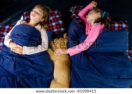 Camping kids and a puppy sleeping in a tent.