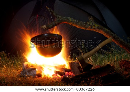 Camping kitchenware - pot on the fire at an outdoor campsite
