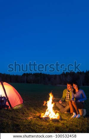 Camping night couple cook by campfire backpack in romantic countryside