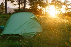 Camping on in the forest during the sunset or sunrise. Bright sunlight.