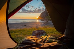 Camping on the Beach at Sunset. Spectacular sunset view to rugged mountain peaks above Kvalvika - famous surfing beach at Lofoten islands, Norway. Lifestyle summer journey vacations