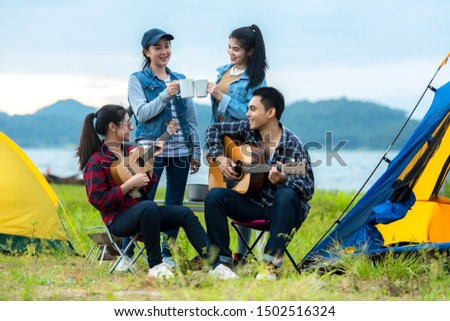Camping outdoor. Group  friends camping leisure and destination travel. Family people sitting around camp fire and playing guitar and roasted sausages, tourism relax and travel near river in holiday.