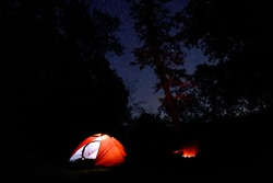 Camping place, campsite with illuminated orange, red tent in forest at night with stars. Holidays on nature outdoors. Beautiful night sky with stars. The Milky Way, deep mysterious space, galaxy.