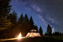 Camping site in mountain valley at night. Silhouette of man hiker standing in front of tourist illuminated tent at burning bonfire under night blue starry sky with Milky way. Pine trees on background