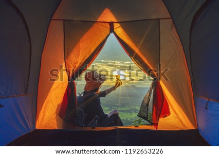 Camping tent in campground at the mountain with sunset,Sunset inside a Tent,Tourist tent in forest camp among meadow on cliff, couple camping in their tent on holiday;Vacation Concept #1192653226