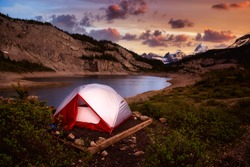 Camping Tent in the Iconic Mt Assiniboine Provincial Park near Banff, Alberta, Canada. Canadian Mountain Landscape in Background. Sunset Sky. Concept: Adventure, Hiking, Backpacking, Freedom