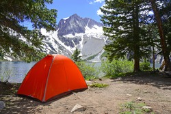 Camping tent in the Rocky Mountains with lake and snow capped peaks