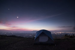 camping tent on mountain and sunset with moon,star and city town.Camping concept