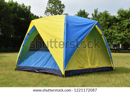 Camping tent setup on green field at front of house.