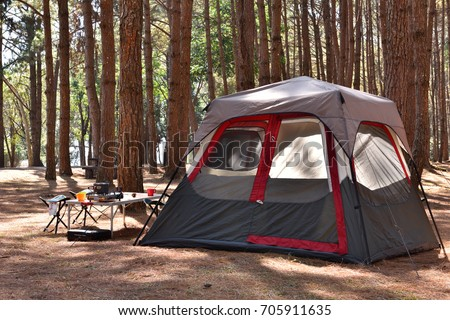 Camping tent with desk and chairs in pine forest #705911635