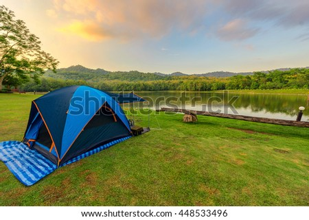 Camping Tents in Nature background with sunset scenic view at lake and forest pine tree