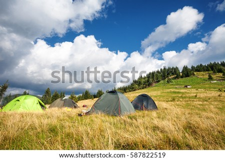 Camping tents on mountain meadow, summer landscape #587822519