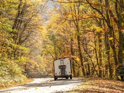 Camping trailer driving down Blue Ridge Parkway with a canopy of colorful fall foliage.