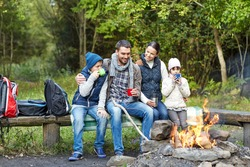 camping, travel, tourism, hike and people concept - happy family sitting on bench and drinking hot tea from cups at camp fire in woods