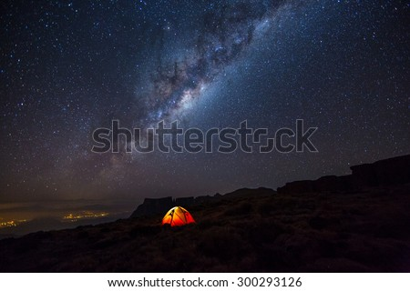 Camping under the stars. The Milky Way stretches overhead the tent high above the villages in the Drakensberg mountains, on the Amphitheatre.