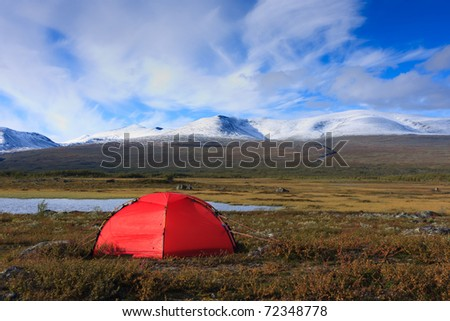 Camping with a red tent in Arctic  wilderness with snow capped mountains. - stock photo