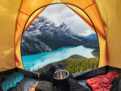 Camping with holding cup in yellow tent open with Peyto Lake in Icefields Parkway at Canada