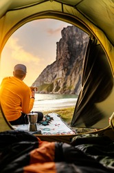 Camping with tent in Lofoten islands, Northern Norway, Kvalvika beach, during sunset. Person sitting in front of a tent holding a hot drink mug.
