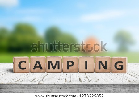Camping word on a wooden cube sign with a blurry background of a campsite in the summer #1273225852
