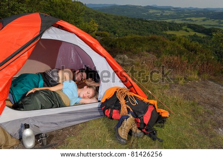 Camping young couple backpackers sleeping in tent with climbing gear