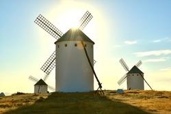 Campo de Criptana windmills illuminated by the sun in the background.