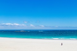 Camps Bay Beach in Cape Town, South Africa. Walking tourists on white sand.