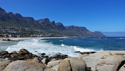 Camps Bay Beach in Cape Town. Turquoise waves foaming in the sand. The mountain range of the Twelve Apostles against the blue sky. Residential area on a slope. Scenic boulders in the foreground