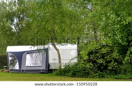 Campside with caravan and a small forest