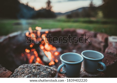 Campsite With Fire Pit and Two Tin Cups with hot tea. Burning Campfire with mountain landscape with evening sunset sky over the forest and hills.