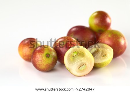 Camu camu berry fruits (lat. Myrciaria dubia) which are grown in the Amazon region (Selective Focus, Focus on the half camu camu in the front and the the complete berry to the left of it)