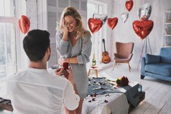 Can not believe this is happening! Surprised young woman covering face with hand and smiling while her boyfriend proposing her in the bedroom