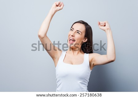 Can not hide her emotions. Beautiful young women keeping arms raised and smiling while standing against grey background