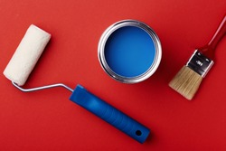 Can of classic blue paint with brush and paint roller on red background. Top view, color of year.