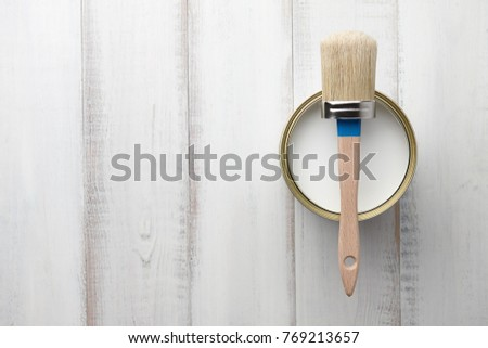 Can of white paint and brush on wooden planks, top view