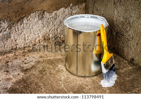 Can of white paint and yellow paintbrush above a rough concrete surface