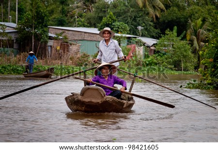 CAN THO, VIETNAM-AUG 27: A senior couple rowing on the river Mekong near Can Tho, Vietnam on August 27, 2010. Nowadays in this area traditional wooden boats are still used as a major way of transport.