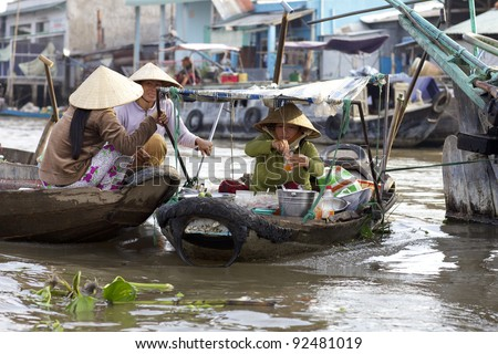 CAN THO, VIETNAM-JAN 7: Vietnamese woman selling cooked food from boat at the Floating Market in Can Tho, Vietnam on January 7, 2012. Cai Rang Market is the biggest floating market in the Mekong Delta