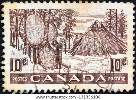CANADA - CIRCA 1950: A stamp printed in Canada shows drying furs, circa 1950. - stock photo