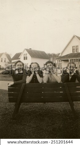CANADA - CIRCA 1950s: Reproduction of an antique photo shows four girls with funny faces, posing on a wooden bench on the background of the street with two-story houses