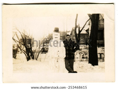 CANADA - CIRCA 1940s: Reproduction of an antique photo shows man posing next to a snowman on the background of the snow-covered streets