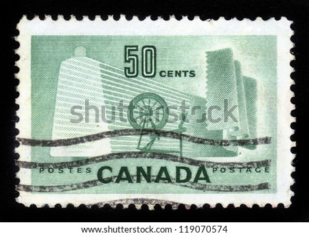 CANADA - CIRCA 1953: stamp printed by Canada, shows old distaff against the background modern manufacturing , circa 1953