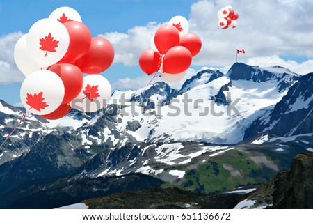 Canada day Maple leaf balloons floating over the Rocky mountains with a Canadian flag in the distance.   #651136672