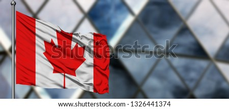 Canada flag waving in the wind against blurred modern building. Business concept. National cooperation theme. #1326441374