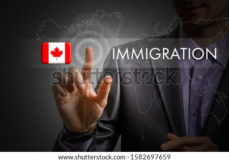 Canada immigration concept. Man pressing virtual button with flag icon Сток-фото ©
