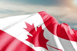 Canada national flag cloth fabric waving on beautiful  sky.