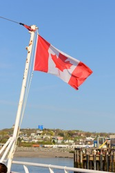 Canada national flag on blue sky. Photo taken on the ferry across Bay of Fundy from Saint John, NB to Digby, NS in Atlantic Canada.