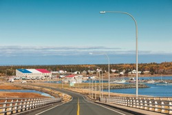 Canada, New Brunswick, Miscou Island. Miscou Harbour Bridge with view of harbor buildings with Acadian colors.