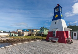 Canada, Nova Scotia, Cabot Trail. Cheticamp, town lighthouse painted in Acadian colors.