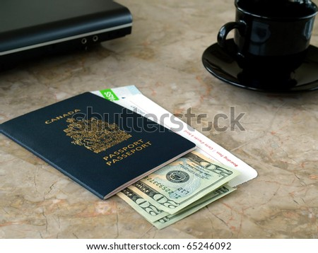 Canada passport with boarding pass, dollar bills  on the table