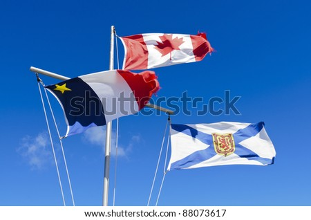Canadian Flag Acadian Flag and Nova Scotia flag blowing in the wind against blue sky